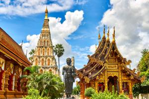 A statue in the center foreground of a man in monks robes holding a staff in his right hand and a basket in the crook of his left arm and holding possibly a parasol folded onto his shoulder. He his facing the viewer. To the left of the statue is a Thai temple as well as a golden one to the right and a white one filled with mini statues wearing orange robes in the background with blue skies and clouds in the background and bits of greenery including a palm tree spread throughout. Taken, according to the photographer at Wiang Kum Kam, ตำบล ช้างเผือก, Thailand