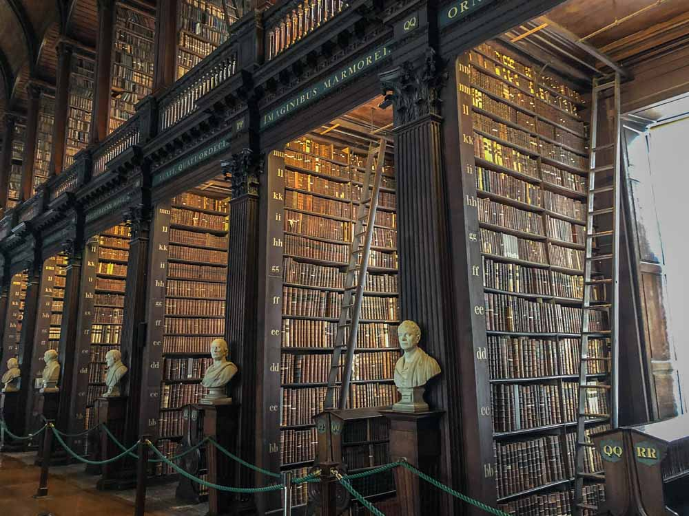 Dublin Ireland itinerary- Trinity College long library bookshelves with white statues