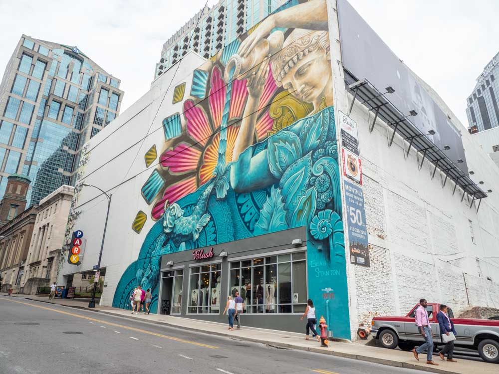 Beau Stanton mural - downtown nashville. Woman pouring water, pink and turquoise color