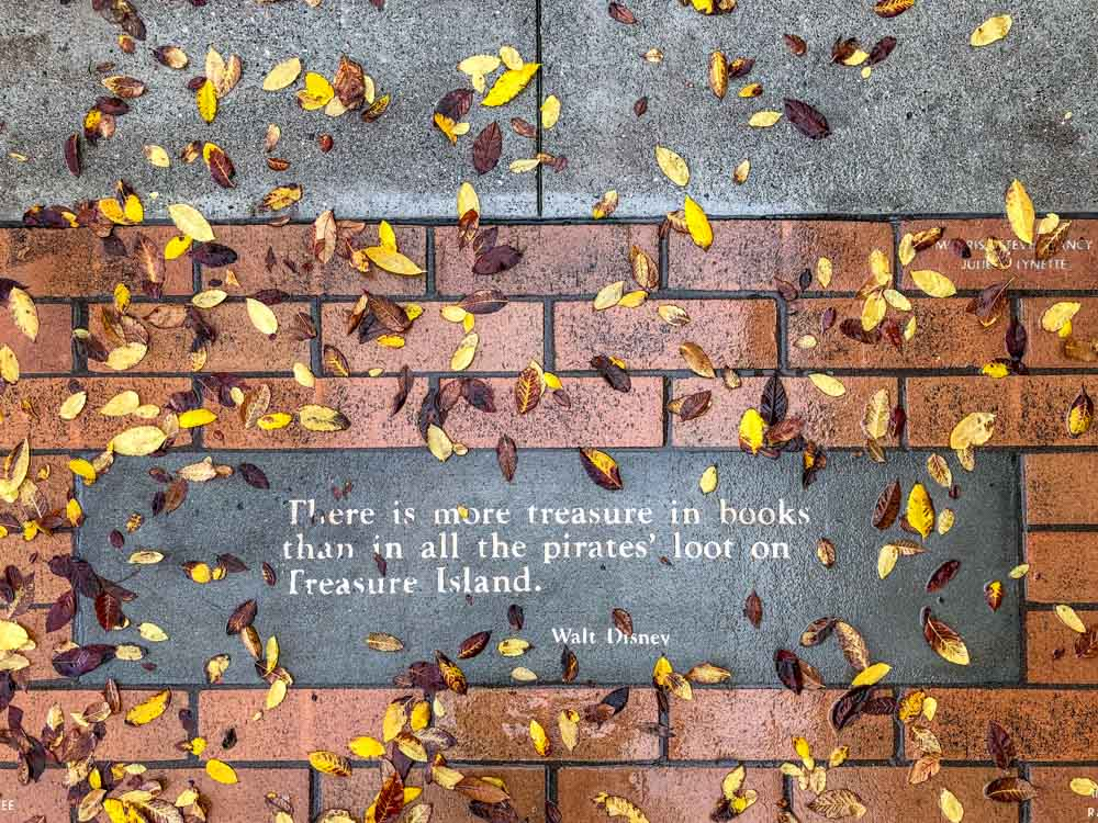 There is more treasure in books than in all the pirates' loot on Treasure Island. Walt Disney book quote. Leaves and brick.