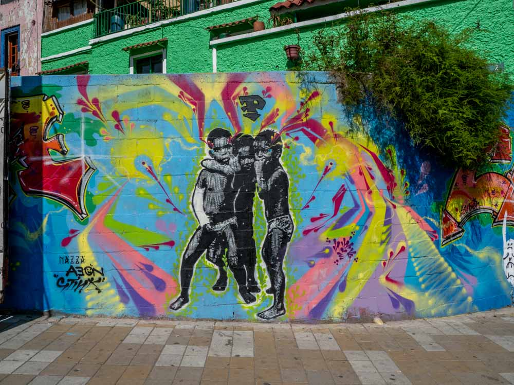 Street art Bogota- three boys by Nazza on multicolored background