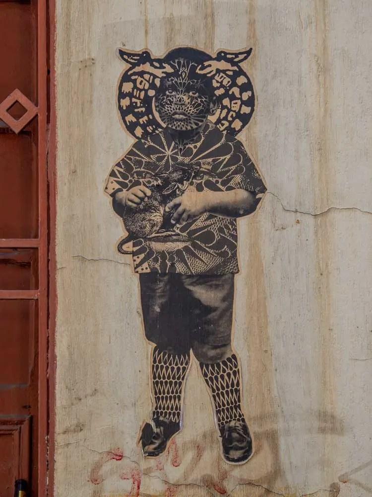 Sinkfish stencil in Bogota. Boy holding a rat