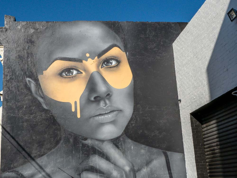 Melbourne street art mural by Fin Dac. Grey woman with yellow mask