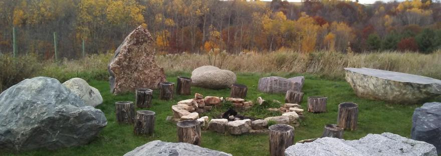 gathering place with rings of stones beside a forest in fall colors