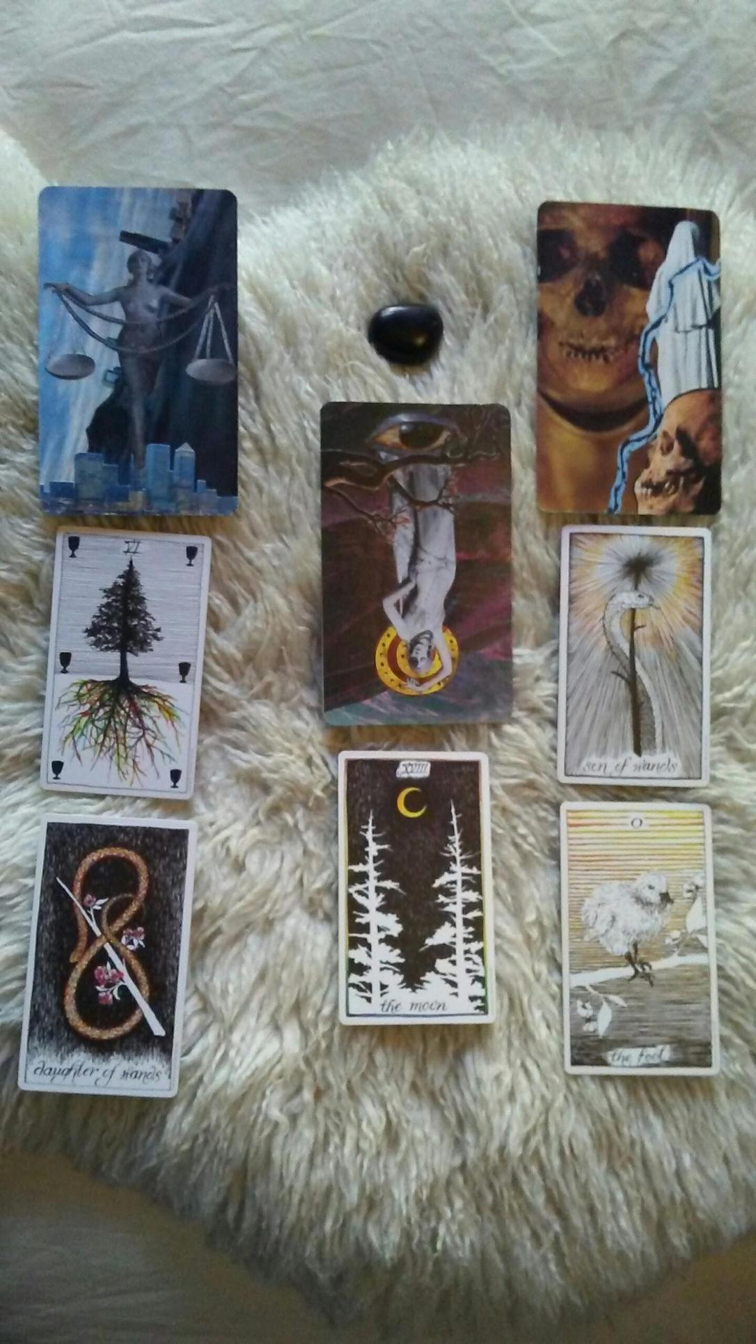 eight mixed tarot cards laid out in a spread with a black stone on a sheepskin