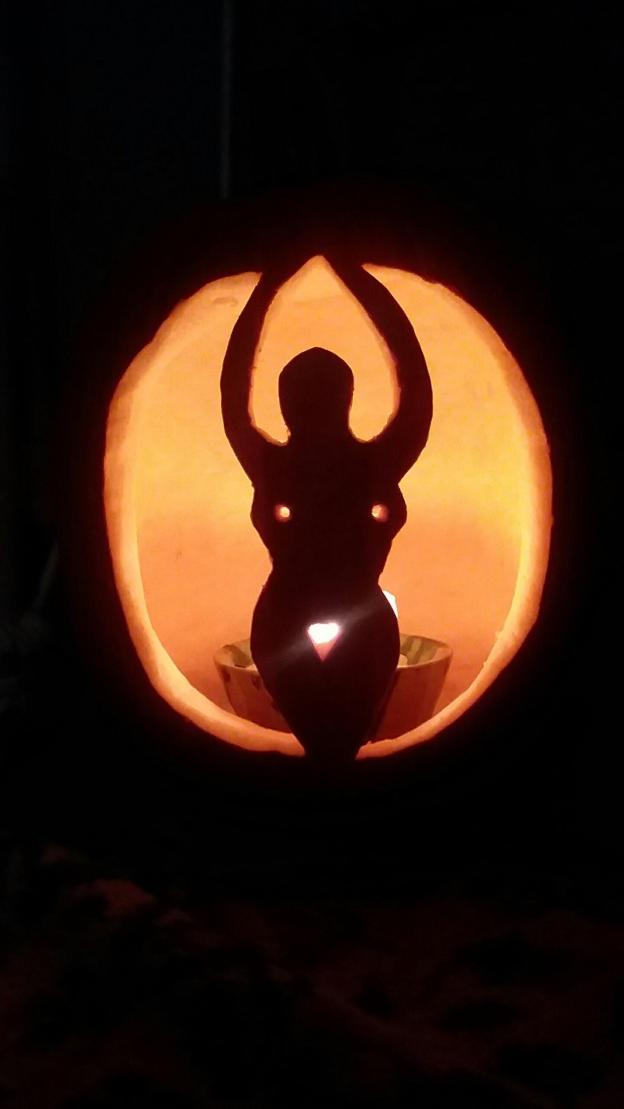 pumpkin carved with a goddess figure lighted by a candle jack-o-lantern