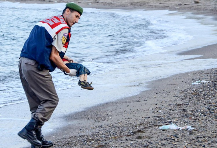 A Turkish police officer carries a migrant child's dead body off the shores in Bodrum, southern Turkey, on Sept. 2 after a boat carrying refugees sank while reaching the Greek island of Kos. (AFP/Getty Images)