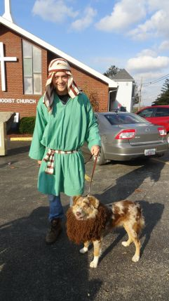 """Man dressed in clothes from Biblical times with his pet dog in a lions mane """"Daniel and the Lion's Den"""""""