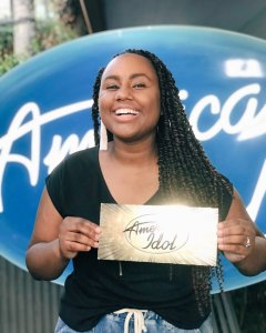Jamie Grace Harper standing in front of the American Idol logo backdrop, holding her golden ticket, sending her to Hollywood