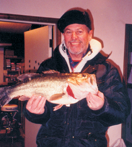 """One evening in January, ice fishing on the Wabash River, Jim Crow of Bluffton landed this 6lbs. 10oz. largemouth bass. It was caught on a 1-lbs test line tipped with dough ball. Assisting on the landing of this bass was Jim DeHoff. Truth be told..it was caught on a local farm pond north of Bluffton with Jim's special handmade """"Crow Fly"""" (sold exclusively at The Bluffton Gun Shop, Bluffton). Barney from The Bluffton Gun Shop said he thinks this bass could actually turn his head and sing!"""