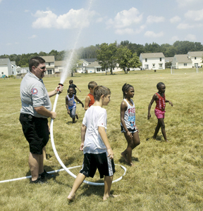 """The participants of Holy Scripture Lutheran Church's """"Bible Soccer Camp"""" get hosed down by Southwest Station 1 Fire Fighters Tom Goodwin and Doug Scott at the Church's soccer fields. The temperature soared to over 100 degrees on Wednesday, July 22, 2011."""