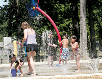 Making a big splash and cooling off is Rachel Aguilar and children Natalie, Connor, Dawson and Katelyn. Temperatures reached a high of 90 degrees at the newly remodeled Splash Pad in the Waynedale Park.