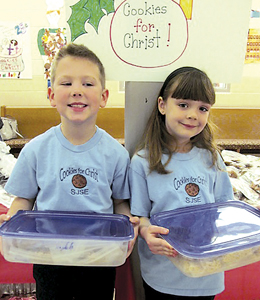 """First graders Parker Schimmele and Addeson Steffen put on a big smile as they brought in their cookies to sell at the annual """"Cookies for Christ"""" sale."""