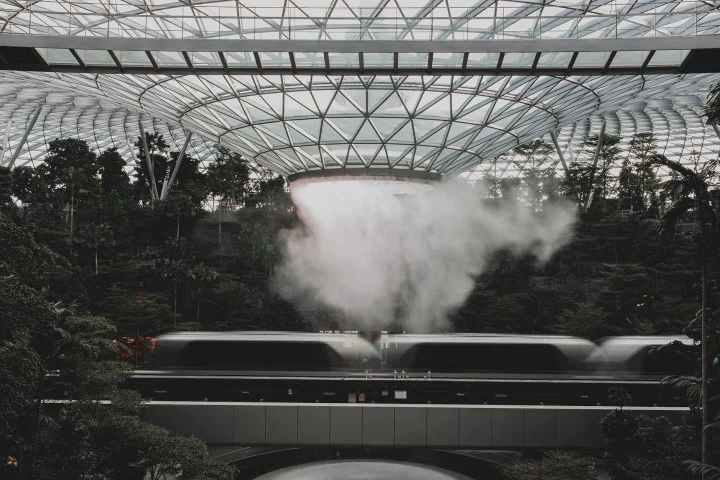 modern train riding under indoors waterfall in modern airport