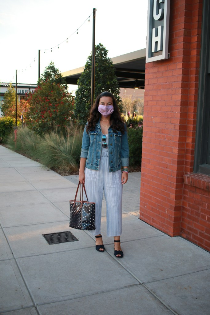 jumpsuit styled with denim jacket and sandals