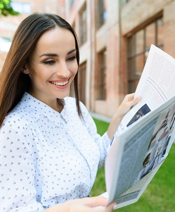 Woman smiling and reading newspaper