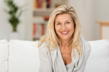Middle aged woman sitting comfortably at home and smiling