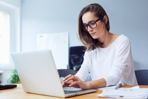 Concentrated woman working on laptop