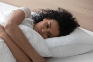 sad or depressed woman laying down in bed