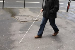 Man walking on sidewalk with a white cane.