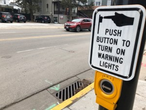 """A sign reading """"push button to turn on warning lights"""" mounted above a button on a street pole."""