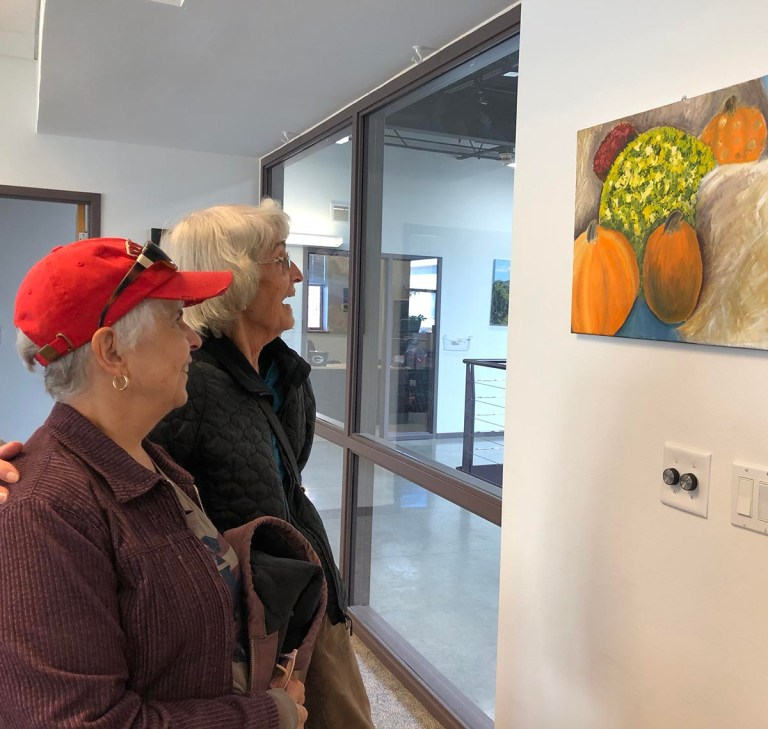 Two older women look at a painting by Aurora Mendez.