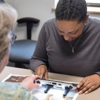 Woman Receives Instruction About How to Use a Magnifier During a Low Vision Evaluation