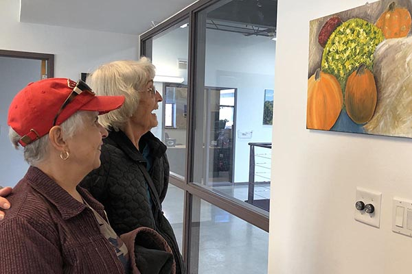Two women look at a painting by Aurora Hernandez