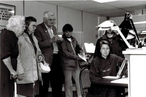 A group of people stand around a person demonstrating a task lamp.