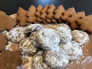 Pfeffernüsse cookies in the center of a light brown plate with gingerbread holiday trees around the edge of the plate.