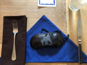 A place setting with a blue napkin folded in a triangular shape and a blindfold resting on top of it.