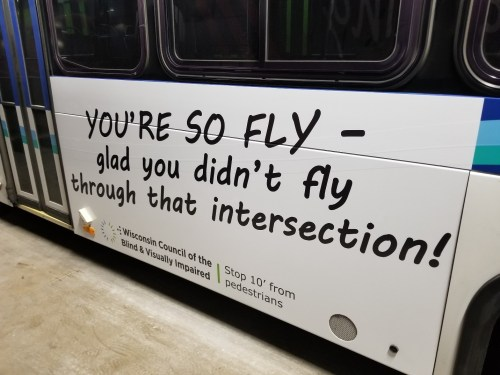 A side of a bus with an ad saying: You're so fly – glad you didn't fly through that intersection.