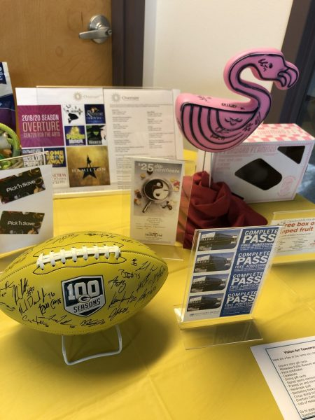 A Packers-signed football, a pink flamingo and other miscellaneous items sit on a table.