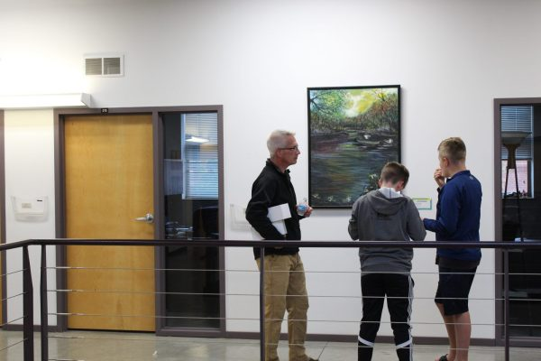 Two boys and a man stand in front of a large oil pastel painting.