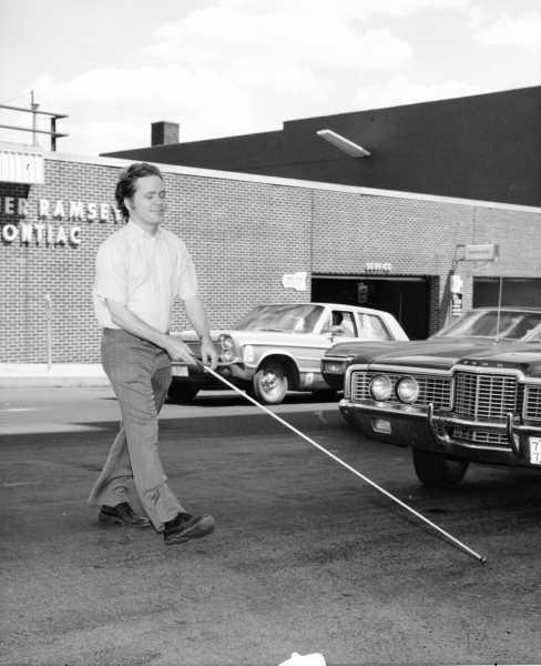 A man walking with a white cane circa 1964.