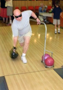 A man bowls wearing dark glasses and using a guide rail.