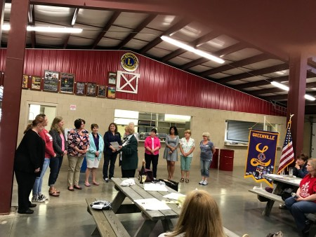 A group of women stand surrounded by Lions Club signs.