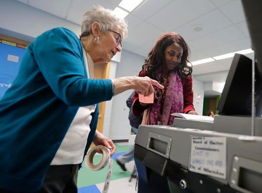 A woman helps another woman use an accessible voting machine.