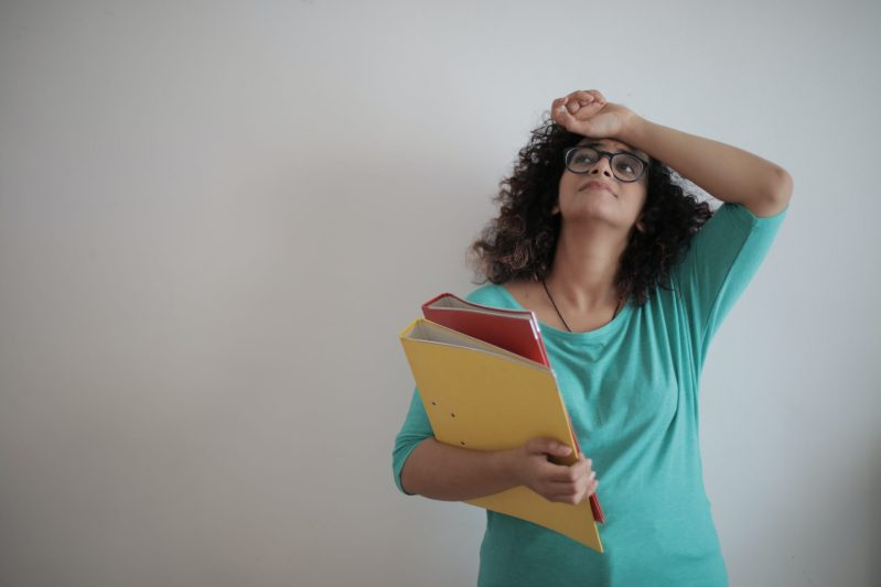 Woman with glasses holding binders looking overworked.