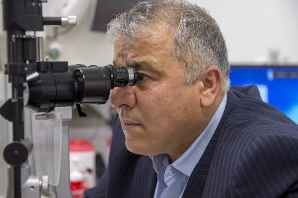 Man looks into an eye exam machine.