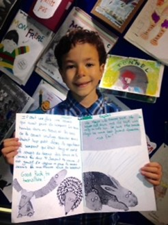 Oskar showing the work of the Paris children, at the Winter workshop exhibition in Church Street Library, December 2015