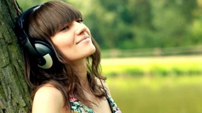 stock-footage-woman-with-headphones-listen-to-the-music-in-the-park