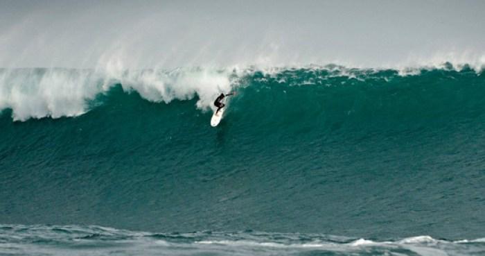 Um surfista descendo uma onda gigante em Punta de Lobos