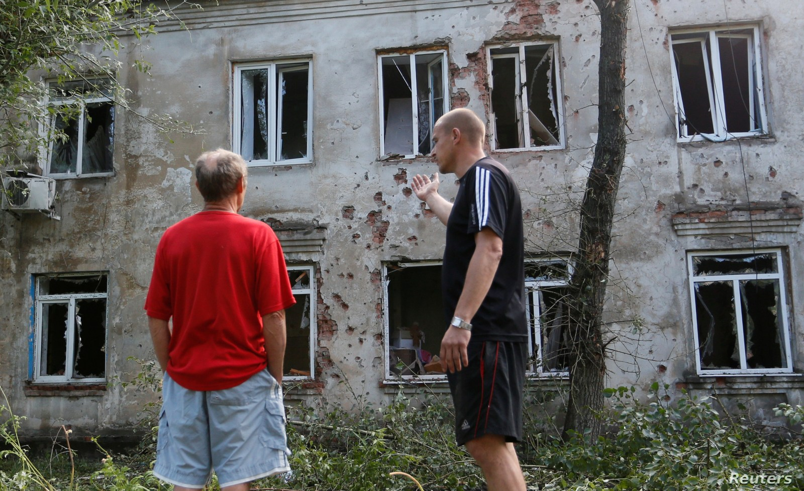 FILE - Men speak outside a residential building, which locals said was damaged during a recent shelling, in the suburb of the rebel-controlled city of Donetsk, Ukraine, June 28, 2019.