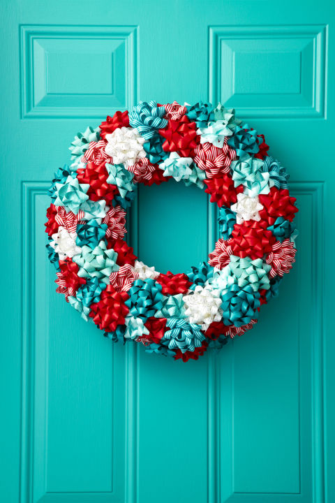 "To turn store-bought bows into a jolly wreath, first attach a loop of floral wire (for hanging) around a 16"" Styrofoam wreath form ($3.99; save-on-crafts.com). Then, hot glue gift bows to the front and sides of the form. Keep it festive with a classic red-and white combo or mix in powder blue for a wintry look."