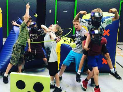 Excited kids holding bows with foam arrows and safety maska at Archery Addiction for a Birthday