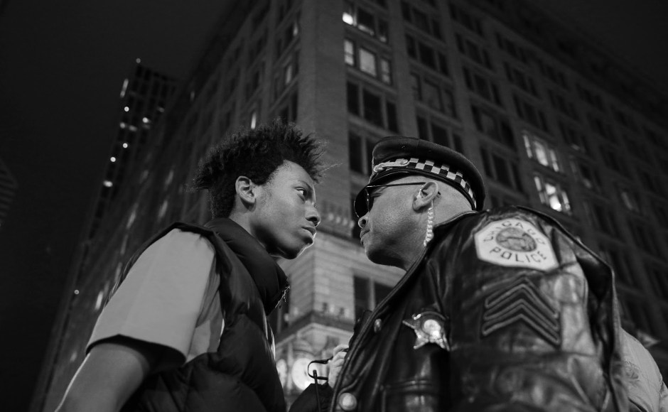 Lamon Reccord, left, scolds a police sergeant during a police violence protest and march at State and Randolph streets Wednesday, Nov. 25, 2015, in Chicago.(John J. Kim/Chicago Tribune)
