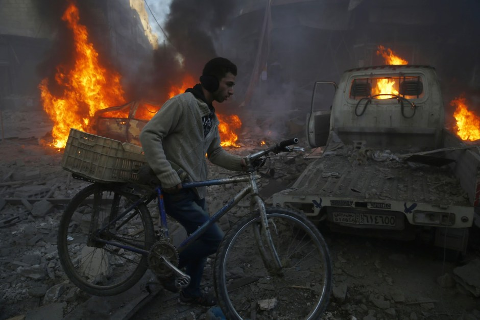 A man carries his bicycle past debris and burning cars following reported airstrikes in the town of Hamouria in the eastern Ghouta region, a rebel stronghold east of the Syrian capital Damascus, on December 9, 2015. The Syrian Observatory for Human Rights reported at least 11 civilians, including four children, were killed in strikes on the town of Hamouria, but said it was unclear if they were carried out by Russian or regime aircraft. AFP PHOTO / SAMEER AL-DOUMY