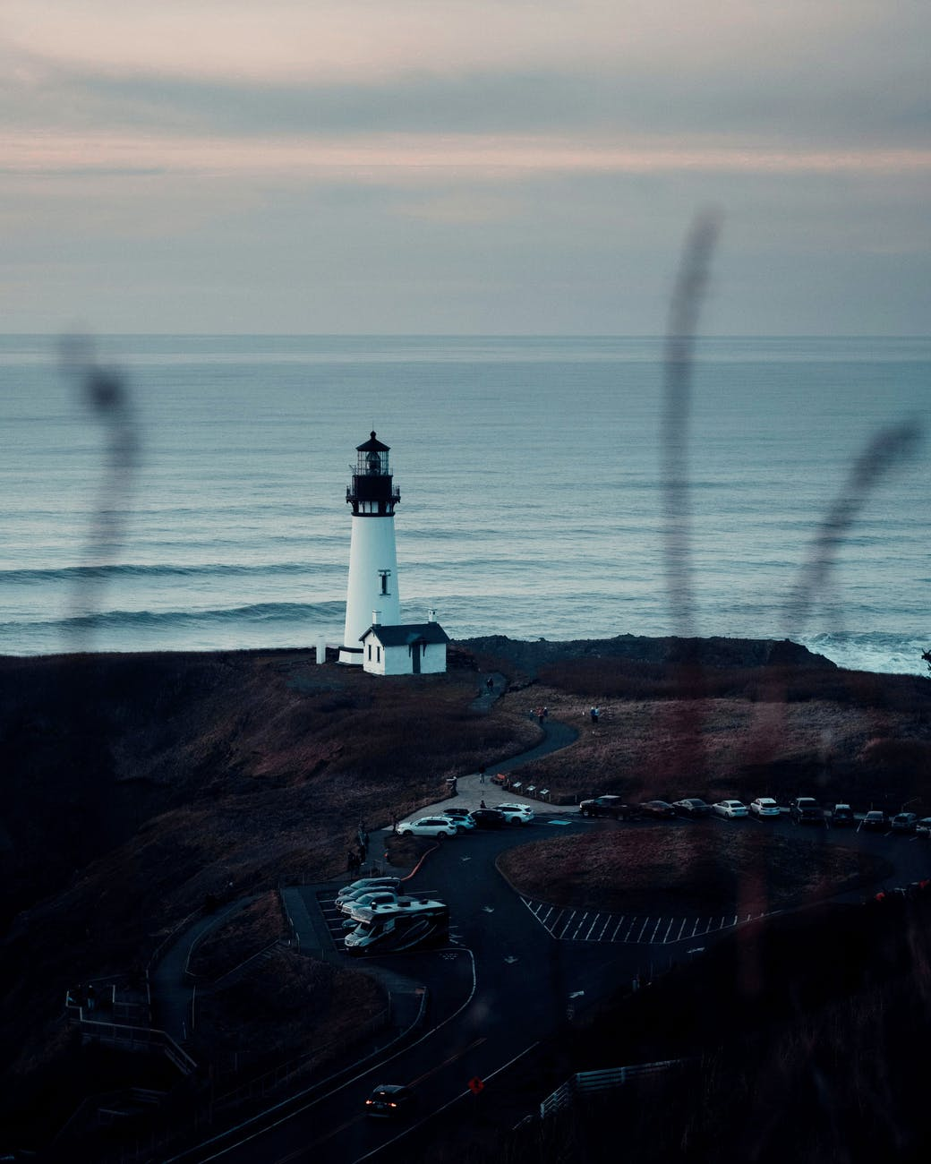 lighthouse on seashore under cloudless sky