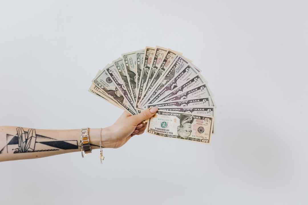 hand holding fan of us dollar bills